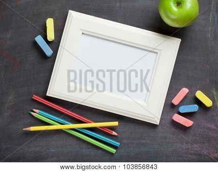 Photo frame and school supplies on blackboard background. Top view with copy space