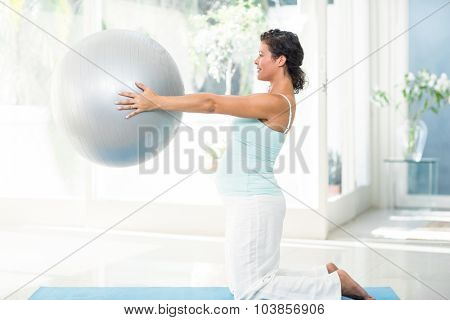 Full length of pregnant woman holding exercise ball at fitness studio