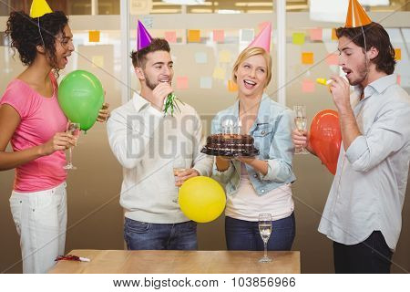 Colleagues enjoying birthday party in creative office