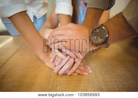 Midsection of family holding hands on table