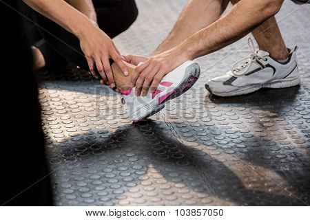 Cropped image of man holding leg of an injured woman at the gym