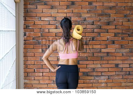 Young latin woman in a yoga studio indoors, against a brick wall, with a yoga mat.