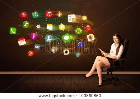 Business woman sitting in office chair with tablet and colorful app icons concept on background