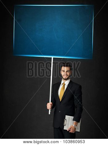 Young businessman holding a big, blue board