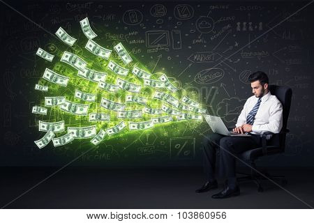 Businessman sitting in chair holding laptop with dollar bills coming out concept on background