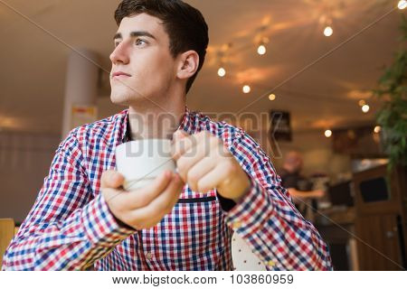 Low angle view of young man holding coffee cup at cafe