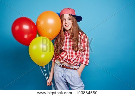 Pretty adolescent girl with balloons looking at camera