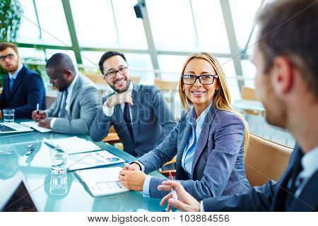 Pretty young businesswoman in suit and eyeglasses looking at her colleague during talk