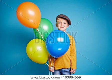 Little boy with balloons looking at camera