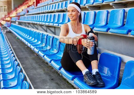 Happy fit woman with container of water having break after workout