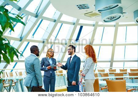 Group of modern employees interacting in office