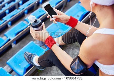 Fitness lover using iphone at stadium