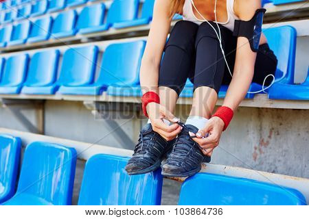 Sporty girl with iphone tying shoelace on sneaker