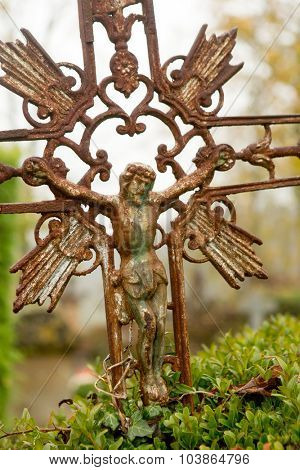 Detail of a rusty tombstone cross in a medieval French graveyard