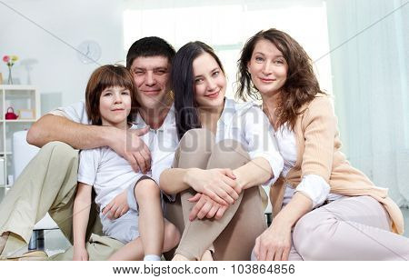 Affectionate family of four looking at camera at home