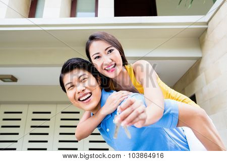 Chinese man carrying his girl piggyback at new house, she is showing the home keys