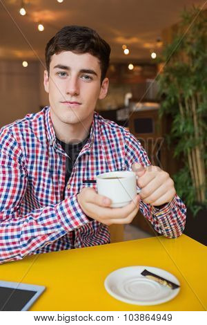 Portrait of young man holding coffee cup at cafe