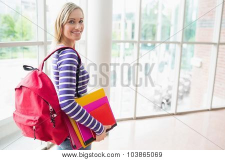 Portrait of confident female student with backpack and books in college