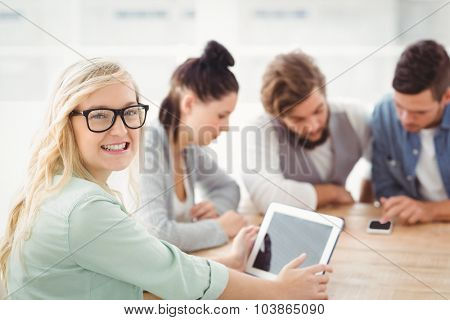 Portrait of smiling woman wearing eyeglasses holding digital tablet at office