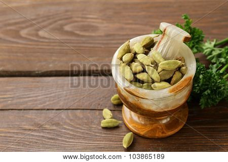 cardamom  in a stone mortar on a wooden table