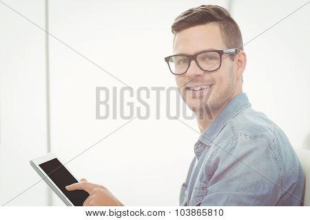 Portrait of happy man wearing eyeglasses while using digital tablet