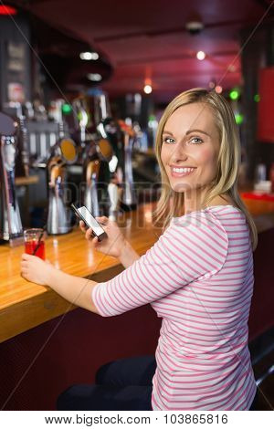Portrait of happy young woman with mobile phone holding glass at bar counter