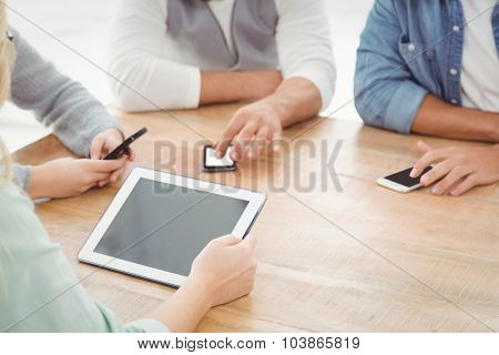 Mid section of people using smartphones and digital tablet at desk