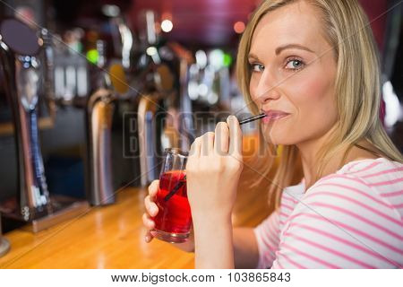 Portrait of young woman sipping drink at bar counter