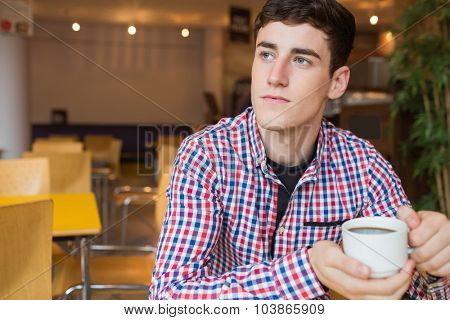 Thoughtful young man holding coffee cup at restaurant