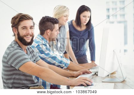 Portrait of smiling man sitting at desk with coworkers working in office