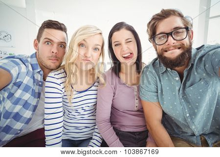 Smiling business people gesturing while taking selfie in office