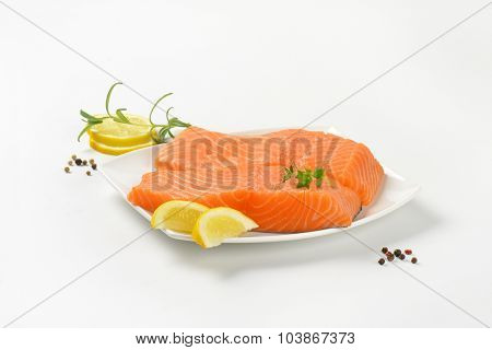 two raw salmon fillets on white square plate