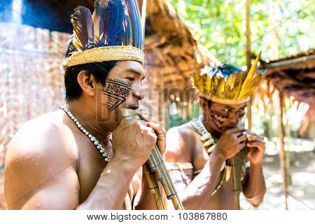 Native Brazilian group playing wooden flute at an indigenous tribe in the Amazon