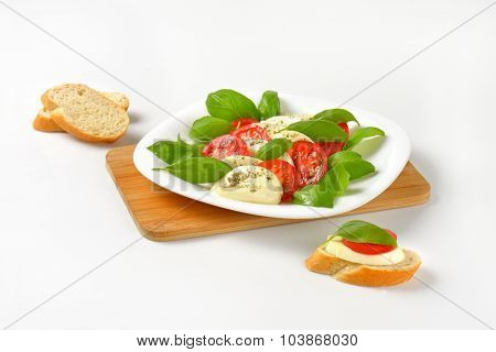 plate of fresh caprese salad with bread on wooden cutting board