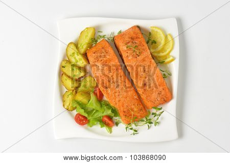 pan fried salmon fillets served with vegetable garnish on white square plate