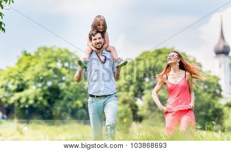 Family walking on meadow having walk, dad is carrying his little daughter on the shoulders