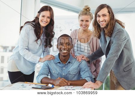 Portrait of smiling business team putting hands on man shoulder at desk in creative office
