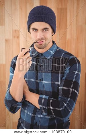 Portrait of confident hipster smoking pipe against wooden wall in office