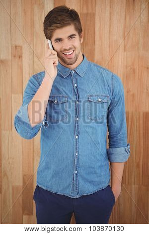 Happy hipster using mobile phone while standing against wooden wall