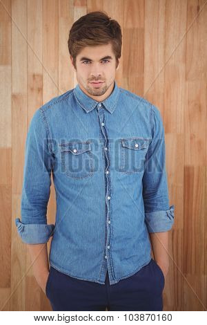 Portrait of confident hipster with hands in pockets standing against wooden wall