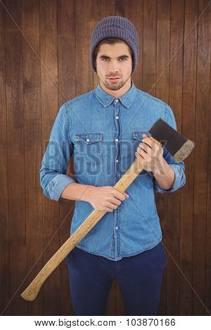 Portrait of serious hipster wearing knitted hat holding axe