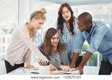 Business team discussing while pointing at diagram in creative office
