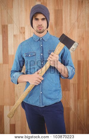 Portrait of serious hipster holding axe while standing