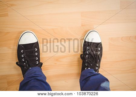 Low section of businessman wearing canvas shoes standing on hardwood floor