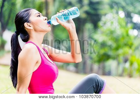Asian woman having break from sport training in tropical park, drinking water from a bottle