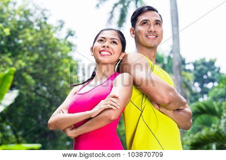Asian woman and man during jogging training standing shoulder to shoulder looking in tropical park