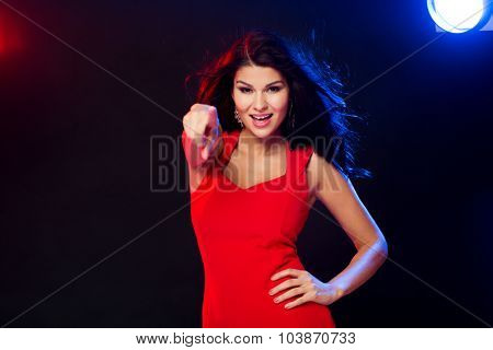 people, holidays, night lifestyle, gesture and leisure concept - beautiful sexy woman in red dress pointing finger on you at  disco in nightclub