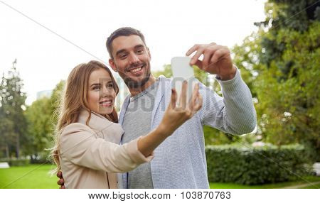 love, relationship, technology and people concept - happy couple with smartphone taking selfie in summer park