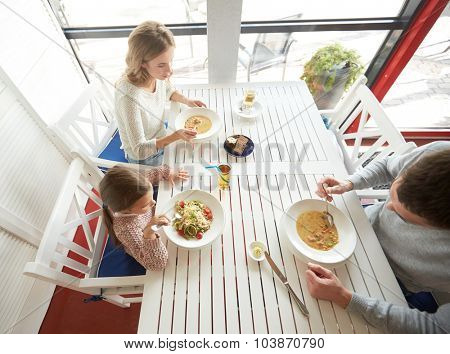 family, parenthood, food and people concept - happy mother, father and little girl eating soup and pasta for dinner at restaurant or cafe