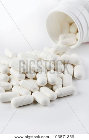 Pills spilling from plastic container